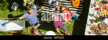 Young people dancing, drinking and eating at a party outdoors - Stock Photo