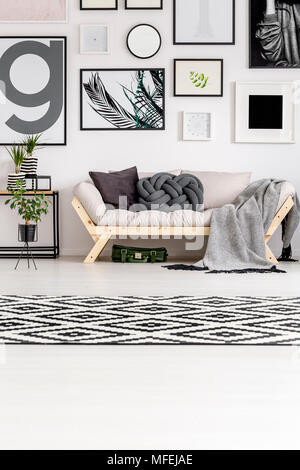 Patterned carpet in black and white living room interior with sofa against the wall with posters