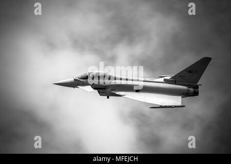A dramatic black & white low fly pass of the Italian Air Force Eurofighter Typhoon in heavy mist and cloud on a warm wet day - Stock Photo