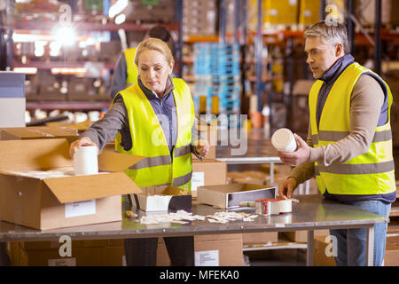 Nice serious people packing boxes - Stock Photo