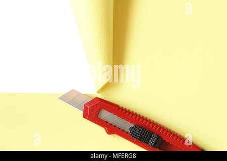 Red office knife cutting yellow paper sheet. Isolated on white with clipping path - Stock Photo