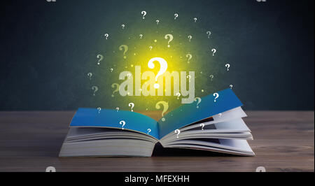 Yellow question marks hovering over open book  - Stock Photo