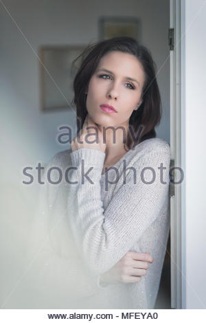 Dreamy young woman staring out of a window with a faraway expression and her hand to her neck - Stock Photo
