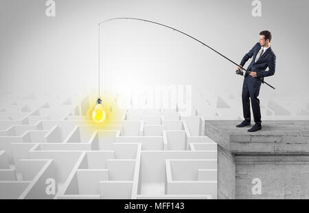 Young businessman fishing new idea concept on the top of a building from a maze - Stock Photo