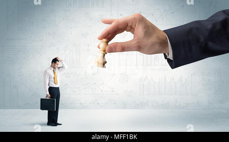 Little businessman is afraid to make the next step in his chess game with graphs, charts and reports background  - Stock Photo