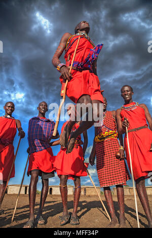 Masai warriors doing traditional dance. A circle is formed and one or two warriors will enter the circle to jump while maintaining  a straight posture - Stock Photo