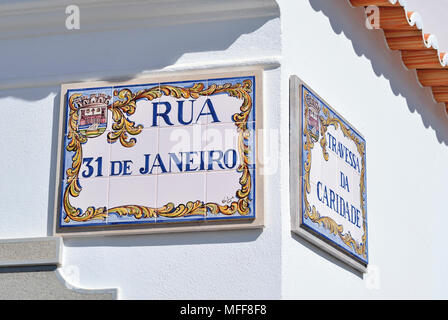 Hand painted  ceramic tiles with road name on white washed house wall - Stock Photo