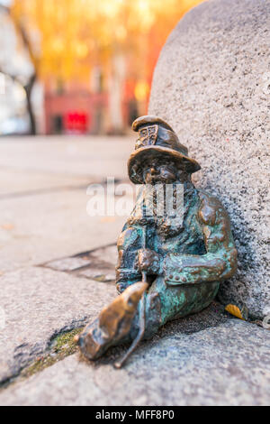 Small copper statue of a dwarf, sitting on the floor of a street in Wroclaw, Poland. Wrocław's dwarfs are famous tourist attraction in the city. - Stock Photo