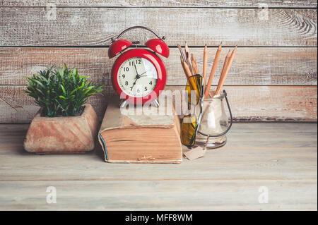 Old book, alarm clock, pencils on a wooden background. Back to school concept - Stock Photo