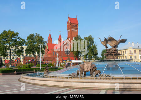 Church Of Saints Simon also known as the Red Church and fountain with name of belarusian city Brest on it at Independence Square In Minsk, Belarus. - Stock Photo