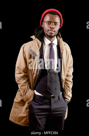 stylish Afro guy in white shirt. black vest, trousers, jacket and red cap looking at the camera. student wearing coat - Stock Photo