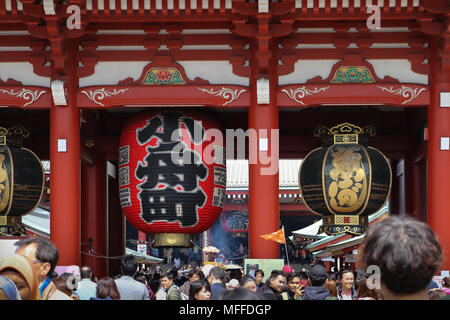 A huge red chochin or paper lantern hangs on the Hozomon Gate of the Sensoji Temple complex in Tokyo, Japan, with two copper toro on either side. - Stock Photo