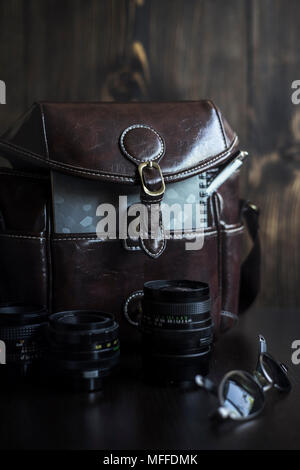 Men's casual outfits with brown camera bag and accessories on wooden background - Stock Photo