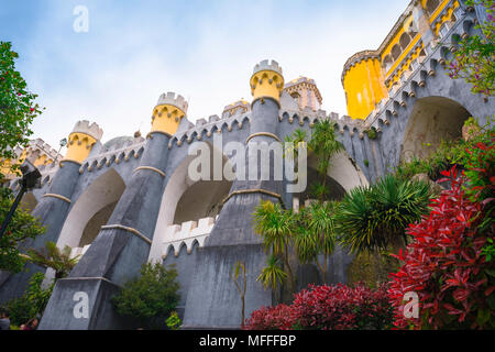 Sintra palace, view of the huge ramparts and buttresses supporting the colorful Palacio da Pena in Sintra, Portugal. - Stock Photo