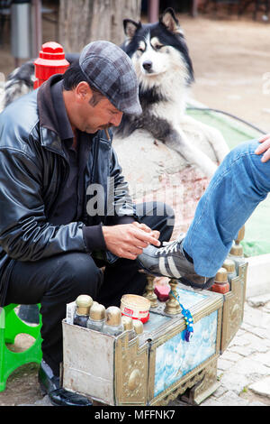 Man is polishing shoes in Antalya, Turkey - Stock Photo