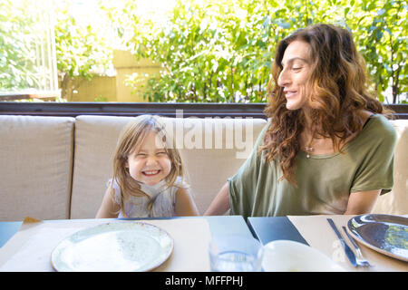 happy family sitting in restaurant: woman mother and her daughter four years old blonde girl laughing with funny face expression - Stock Photo