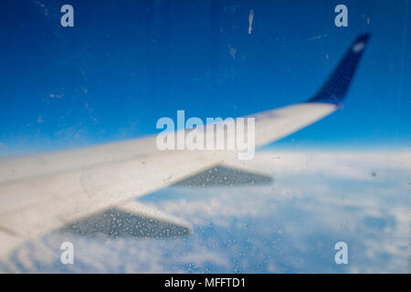 Frozen condensation of ice crystals on the window of an airplane with the wing in the back. - Stock Photo