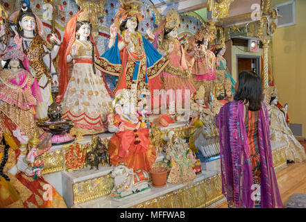 A woman prays at the alter with statues of  Hindu Gods and Goddesses at the Shri Lakshmi Narayan Mandir temple in Richmond Hill, Queens, New York. - Stock Photo