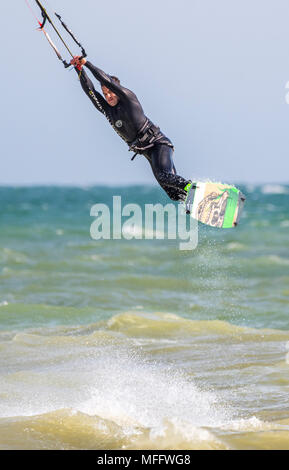 Man performing a stunt while kitesurfing at sea, flying in the air. Portrait view. - Stock Photo
