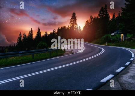 Asphalt road and lonely tree under a starry night sky and the Milky Way - Stock Photo