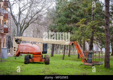Articulated Boom Lift in the grass in a park - Stock Photo