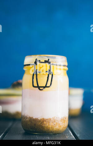 Ombre cheesecake on a jar glass made with three different layer of cheese, acai cream cheese , blueberry and mango pulp, top view on a gray table agai - Stock Photo