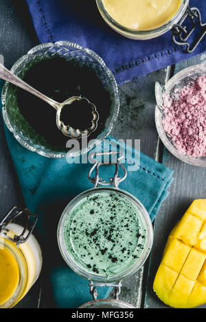 Cheesecake on a glass jar, made with mango and spirulina powder, with chia seeds and coconut powder, over a wooden blue background - Stock Photo