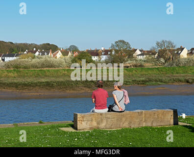 Couple sitting on bench overlooking the River Colne (and Wivenhoe), Essex, England UK Stock Photo