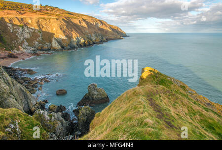 Amazing sea view from the top of the cliffs, Howth Head, near Dublin.Boulders stop the crashing waves, sandy beach, grassy hills and the blue open sea - Stock Photo