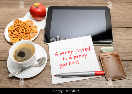 napkin handwriting message proverb on wooden table with coffee, some food and tablet PC A penny saved is a penny gained - Stock Photo