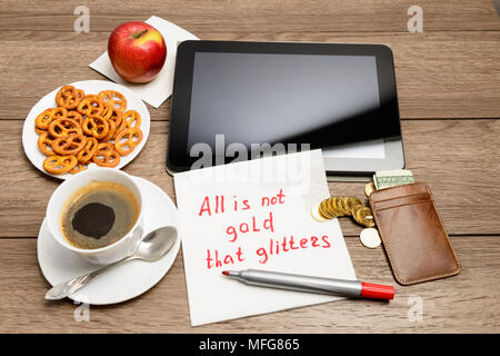 Wooden table with coffee, some food and napkin message proverb All is not gold that glitters - Stock Photo
