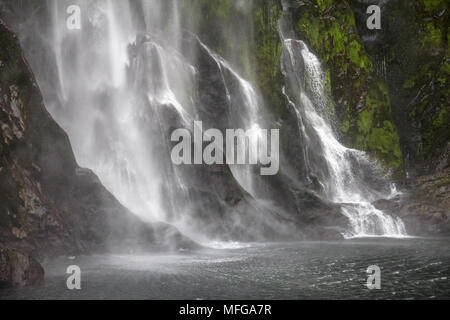 Close-up of waterfall entering Milford Sound, South Island, New Zealand. Having fallen from a great height, water is mostly spray on green mossy rocks - Stock Photo