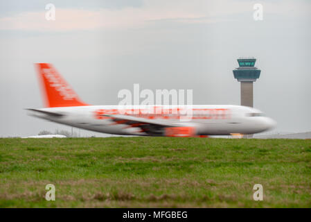A small to medium EasyJet airplane speeds along a runway with motion blur in front of the air traffic control tower at Stansted International Airport. - Stock Photo
