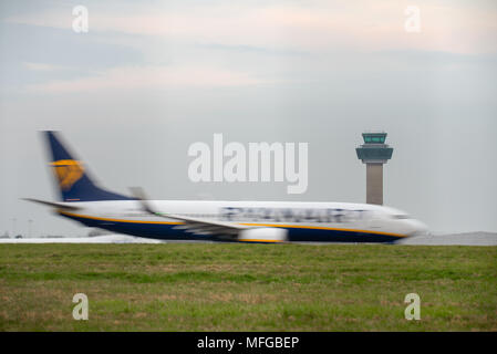 A small to medium Ryanair airplane speeds along a runway with motion blur in front of the air traffic control tower at Stansted International Airport. - Stock Photo