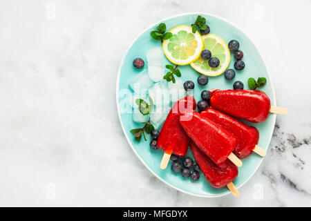 frozen strawberry juice snack ice pop or popsicle on a white marble table with blueberries and ice with mint. summer ice cream fresh food background - Stock Photo