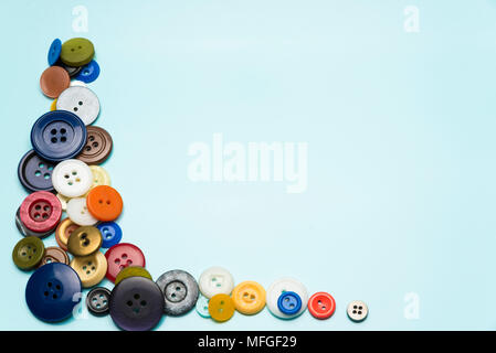 multi-colored buttons lie on a blue surface - Stock Photo