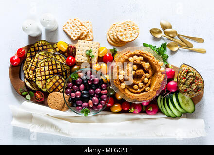 Vegan snack board. Flat-lay of Various Vegetarian dishes  hummus hummus with sun-dried tomatoes , hummus with sun-dried tomatoes with crackers, auberg - Stock Photo