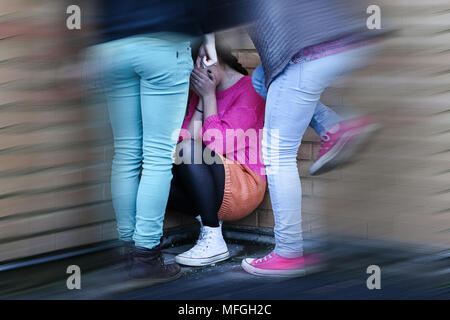 Teenage girls bullying and kicking a girl sitting down covering her face, crying. Blurred. - Stock Photo