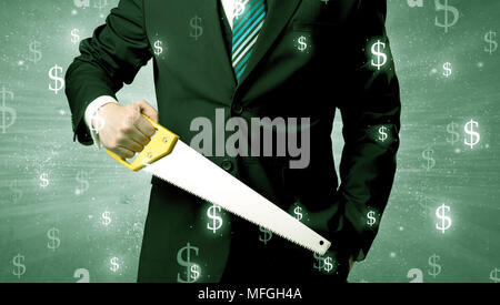 Handsome businessman holding tool with dollar symbols around and with green background - Stock Photo
