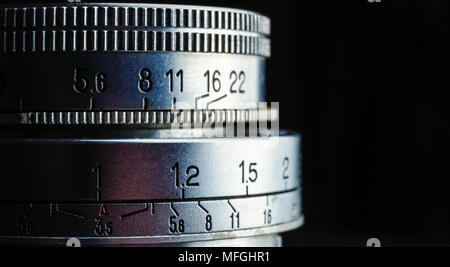 Beautiful closeup of an old vintage camera lens with aperture values isolated on a black background. Photography concept with copy space. - Stock Photo