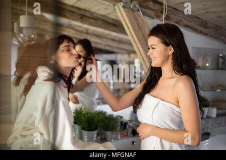 Portrait of beautiful woman doing make up to her friend - Stock Photo