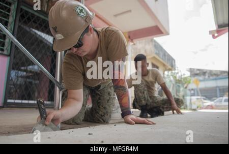 180424-N-OU129-091 TAWAU, Malaysia (April 24, 2018) Builder 3rd Class Autumn Williams of Naval Mobile Construction Battalion (NMCB) 5 and a Malaysian Armed Forces member apply grout to a concrete floor at an engineering project at SK Kebangsaan Taman in Tawau, Malaysia as a part of Pacific Partnership 2018 (PP18), April 24, 2018. PP18's mission is to work collectively with host and partner nations to enhance regional interoperability and disaster response capabilities, increased stability and security in the region, and foster new and enduring friendships across the Indo-Pacific Region. Pacifi - Stock Photo