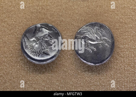 Athena and Pegasus depicted in the Ancient Greek silver coins (Corinthian stater) dated from the second half of the 4th century BC found in Sicily on display in the National Archaeological Museum (Museo Archeologico Nazionale di Napoli) in Naples, Campania, Italy. Athena is depicted wearing the Corinthian helmet. - Stock Photo