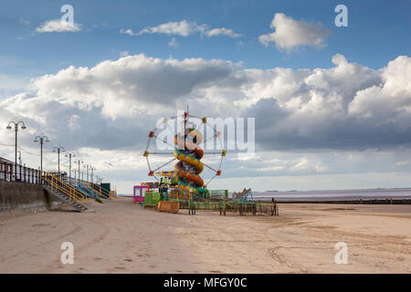 A small funfair attraction shut and closed on a beach landscape in cloudy weather in Cleethorpes, Lincolnshire. - Stock Photo