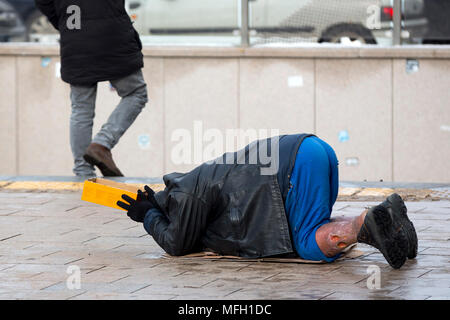 Homeless man with hurt leg on his knees begs for money at the street. Ten years after joining the EU Bulgaria is still the poorest country in the unio - Stock Photo