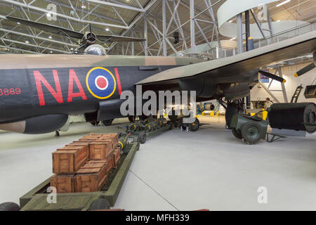 Duxford Imperial War Museum. England, UK.  A Lancaster bomber in an aircraft hanger is ready to be loaded from a train filled with bombs and cases of ammunition. - Stock Photo
