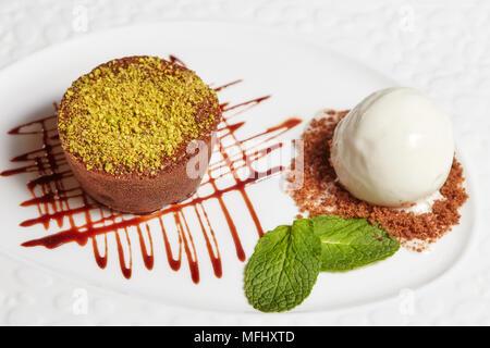 Chocolate brownie cake with vanilla ice cream on white plate, closeup - Stock Photo