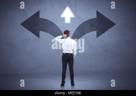 Businessman taking a decision while looking at arrows on the wall concept background - Stock Photo