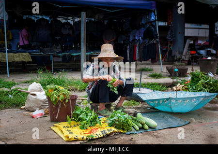 Fuli Village, Yangshuo, Guangxi, China - August 2, 2012: An old chinese woman selling vegetables in a street market at the Fuli Village in the country - Stock Photo