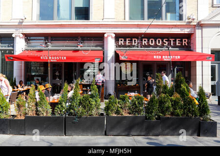 Red Rooster, 310 Malcolm X Blvd, New York, NY. exterior storefront of a soul food restaurant, and sidewalk cafe in Harlem, in Manhattan. - Stock Photo